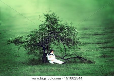 Pregnant woman sitting alone under a beautiful tree in the spring with the concept of time loneliness pregnancy and expectations