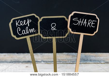 Keep Calm And Share Message Written With Chalk On Mini Blackboard Labels