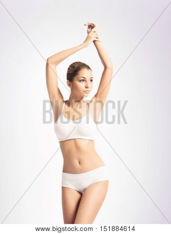 Young, sporty, fit and beautiful girl over gradient grey background.