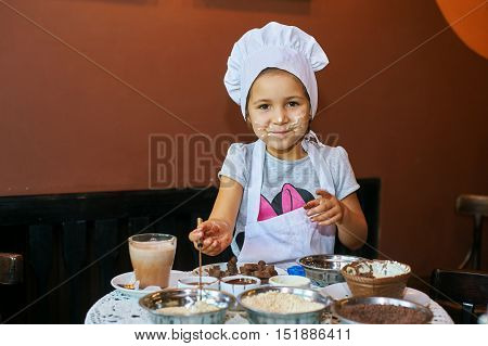 A little girl pastry chef makes homemade candy