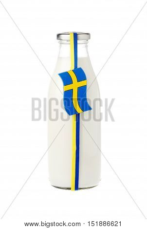 Milk in a classic milk glass bottle decorated with blue and yellow stripes and a Swedish flag isolated on white background.