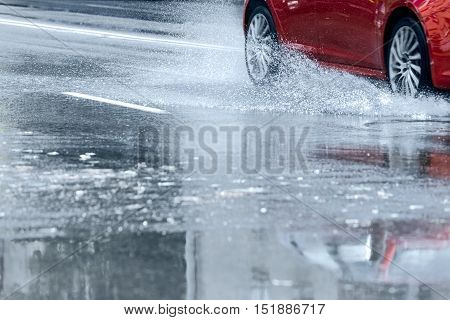 Red Car Driving Through Water Puddle With Water Splashing From Wheels