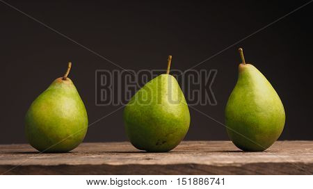 Three delicious green pears on a wooden table