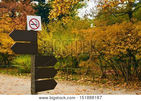 Sign pole with arrows at the crossroad of the walking alleys of a park and no smoking