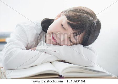 Beautiful Asian girl sleeping on the book