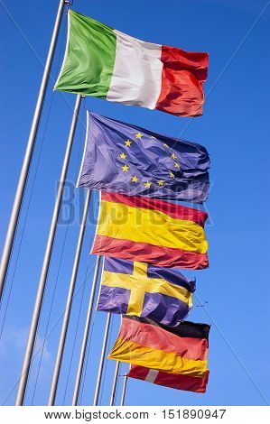 Italian Spanish Swedish German Danish and European flags on a clear blue sky