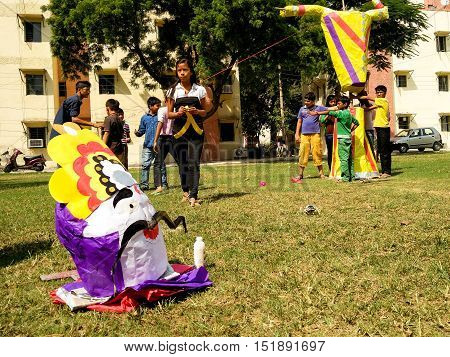 Delhi, India - 11th Oct: Children making a paper machie ravan effigy. Burning this effigy is part of the celebrations for the Hindu festival of Dussera which leads to Diwali