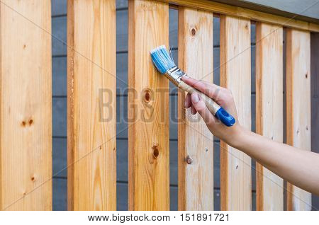 painting terrace railings with a blue paintbrush by hand