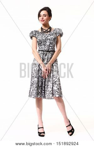 woman with updo hair style in fokrmal party summer print short sleeve dress high heels shoes full length body portrait standing isolated on white