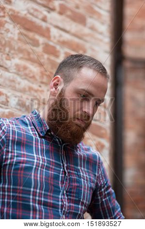 sad young man with beard against the backdrop of a brick wall