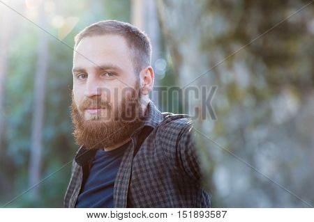bearded man in shirt standing behind a tree in the park