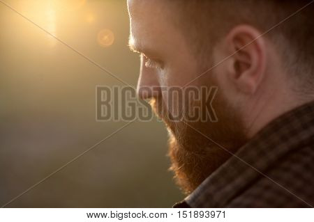 close-up of young bearded men with the rear side view on the background of sunlight and glare