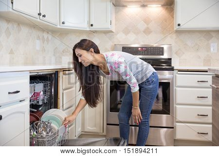 Young Pretty Woman Putting Dishes Into The Dishwasher