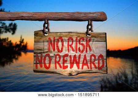 No risk no reward motivational phrase sign on old wood with blurred background