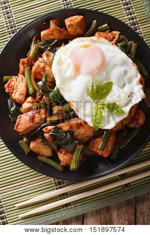 Stir-fry Chicken With Basil, Green Beans And A Fried Egg On A Plate Close-up. Vertical Top View