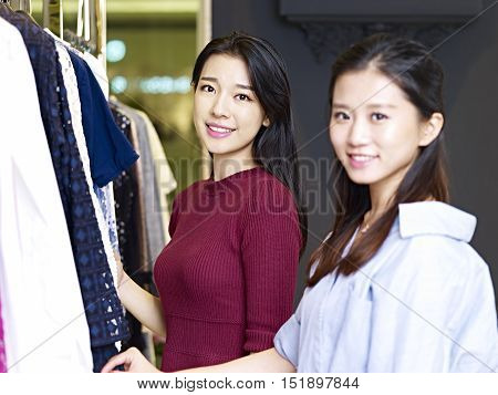beautiful young asian women looking at camera smiling in front of apparels in a clothing shop