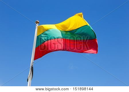 Lithuanian flag waving in thewind on a blue sky.