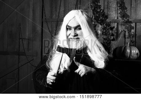 Old wizard with long hair in robe with demonic smile hold ax near finger in wooden house black and white