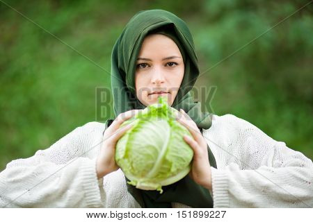 Muslim Vegan Woman with Veil Holding a Savoy Cabbage