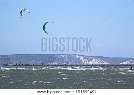 kitesurfers riding in Portland harbour on a windy day