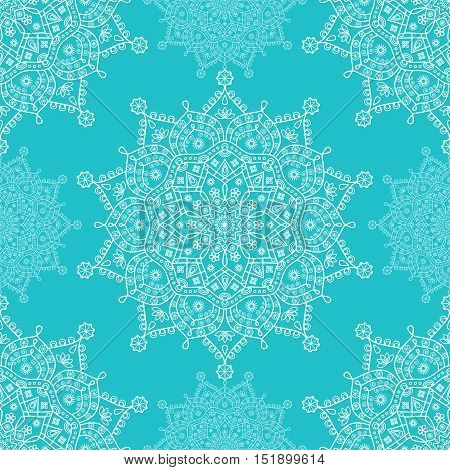 Seamless mandala snowflakes pattern. Winter theme festive  print. White floral snowflakes on turquoise blue background. Lace doily mandala snowflake ornament.