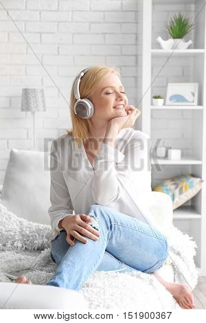 Young woman with headphones enjoying  favorite music and sitting on the couch