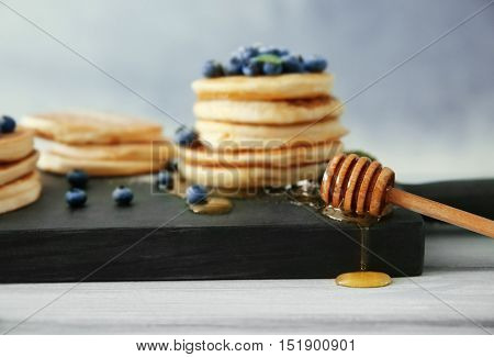 Wooden dipper with honey and delicious pancakes on wooden cutting board