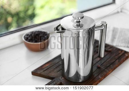 New coffee maker on cutting board on windowsill