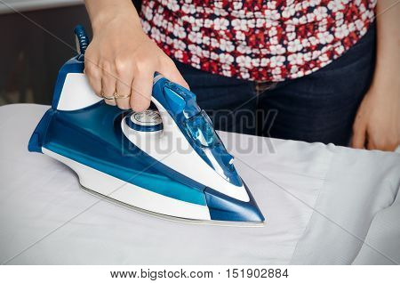 Woman Irons Clothes On Ironing Board With Steaming Iron