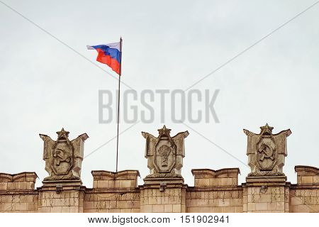 Fragment of parapet administrative government building with USSR symbols, flag of Russia. Emblems with the hammer and sickle a sheaf. Typical architecture of the Stalin era.