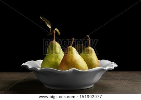 Green pears in plate on black background