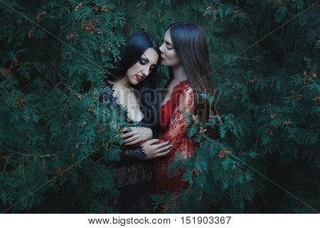 Women lesbians hugging each other among the trees