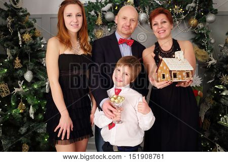 Mother, father, son and daughter pose with gingerbread house during christmas, focus on boy, girl