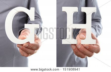 Hands holding letter G and H from alphabet isolated on a white background