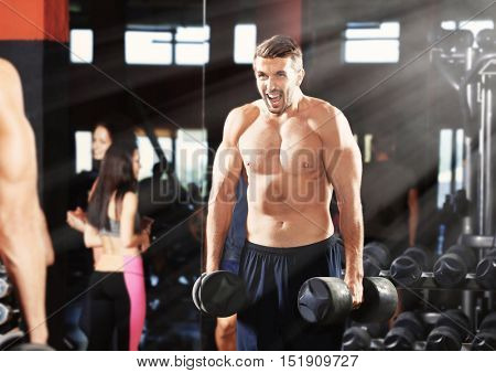 Man flexing muscles with dumbbells in gym