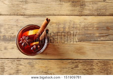 Glass of delicious Christmas mulled wine on wooden background