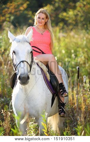 Woman in short pink dress sits arching up on white horse in park
