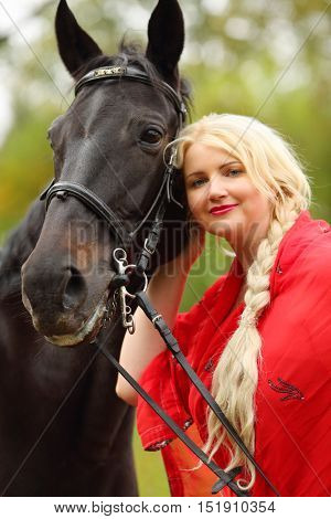 Woman in red dress and blond hair stands near horse in park