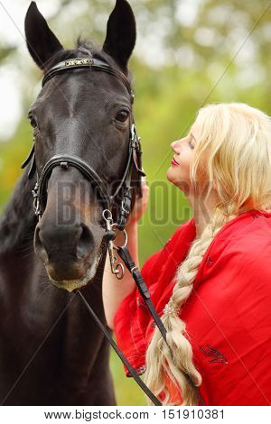 Woman in red dress and long blond hair strokes head of black horse in park