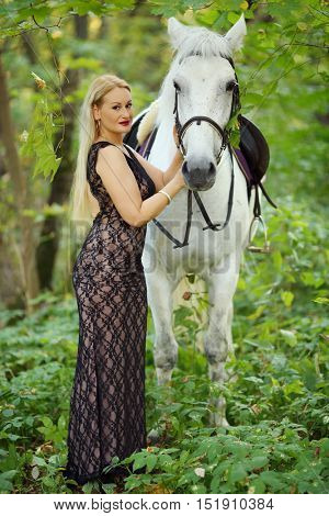 Woman in long black dress stands near beautiful white horse in park