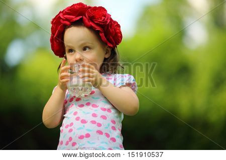 Little cute girl in flower wreath drinks milk in summer park, shallow dof
