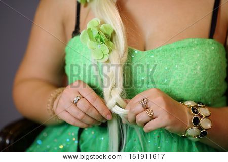 Neckline and hands with gold rings of young woman in green dress