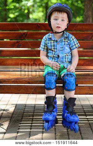 Little handsome boy in roller-blades sits in bench in summer park