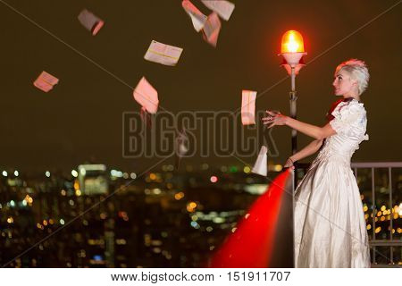 Young woman in white dress stands on high-rise building roof illuminated by red obstruction light and looks at flying thrown out letters.