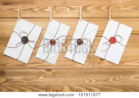 Envelope hanging on rope on wooden background