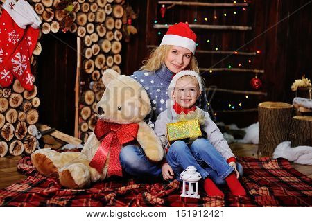 Mother and son in caps of Santa Claus with gifts on the background of the Christmas tree and fireplace