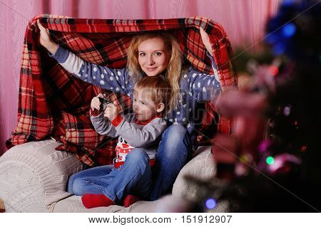 waiting for the Santa Claus. Mom and son playing in the house under a blanket on the background of Christmas tree