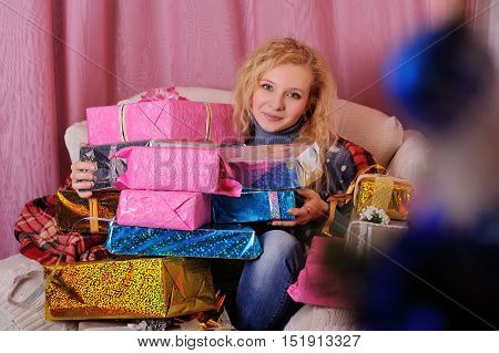 beautiful young woman holding many Christmas gifts in colorful boxes with bows on Christmas tree background.black Friday