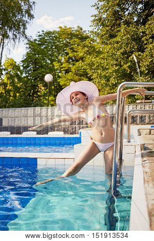 Smiling girl in swimsuit and wide-brimmed hat  stands on ladder to pool.
