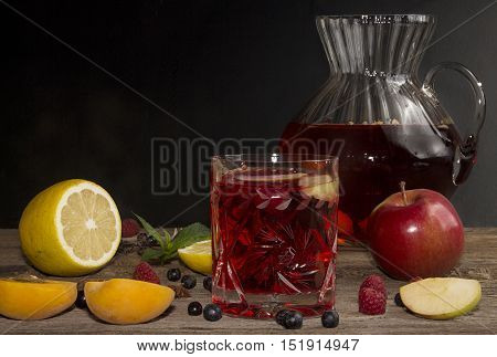 Compot In Glass Jug On Old Wooden Table.